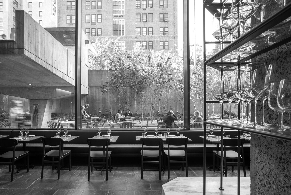 A black-and-white photo of a dining room, facing floor-to-ceiling windows, with shelves of wine glasses in the foreground