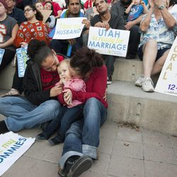 Cidney Marsh, right, kisses her son, Koston Vigil-Marsh, along with her wife, Melissa Vigil during a same sex marriage celebration at Library Square in Salt Lake City, Monday, Oct. 6, 2014.