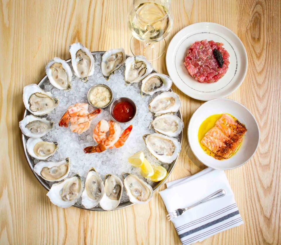 Overhead view of a round silver platter full of raw oysters and accoutrements; it's sitting on a wooden table accompanied by two smaller plates, one with tuna tartare and one with salmon crudo.