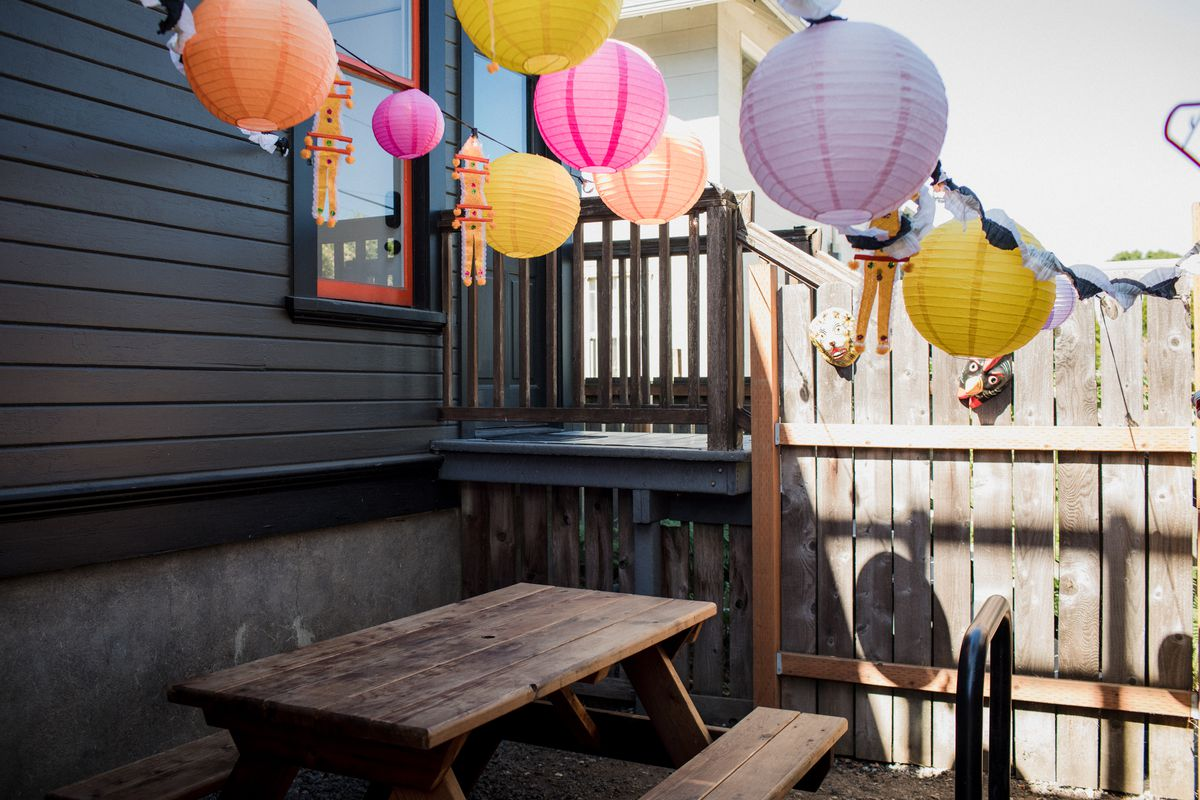 Paper lanterns hang over a picnic table in the back of the restaurant