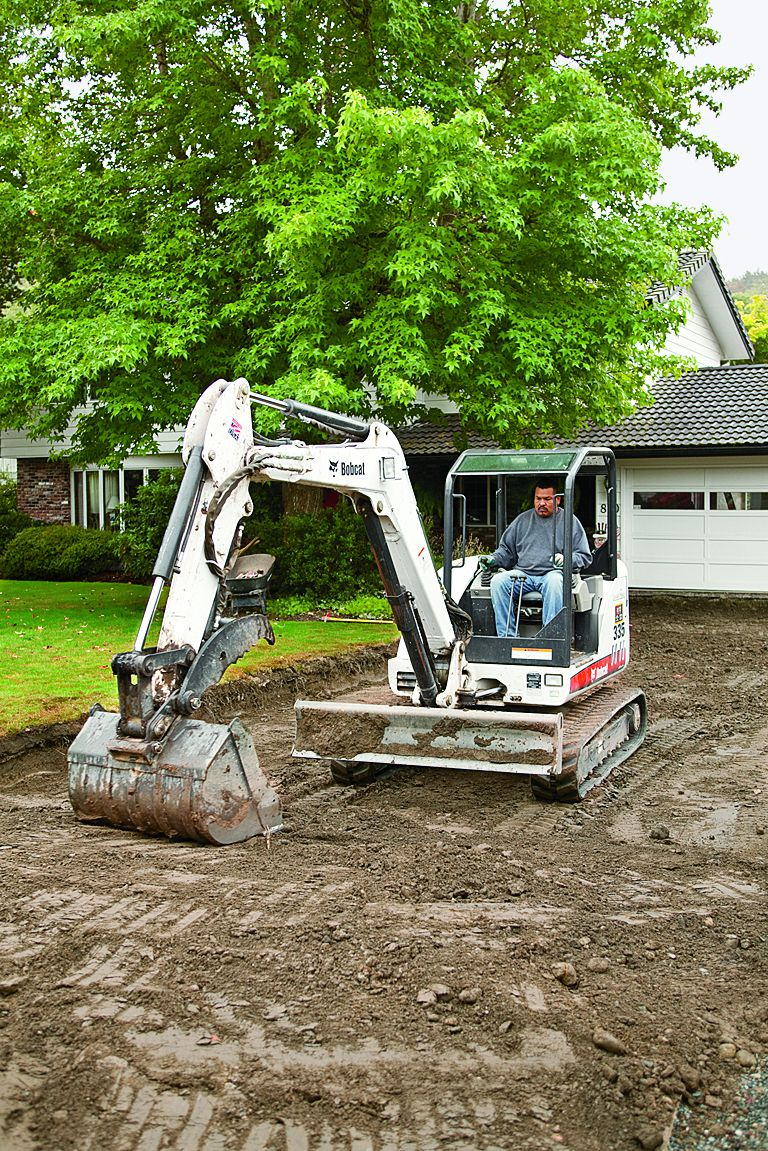 Contractor Excavating Pavement In Driveway