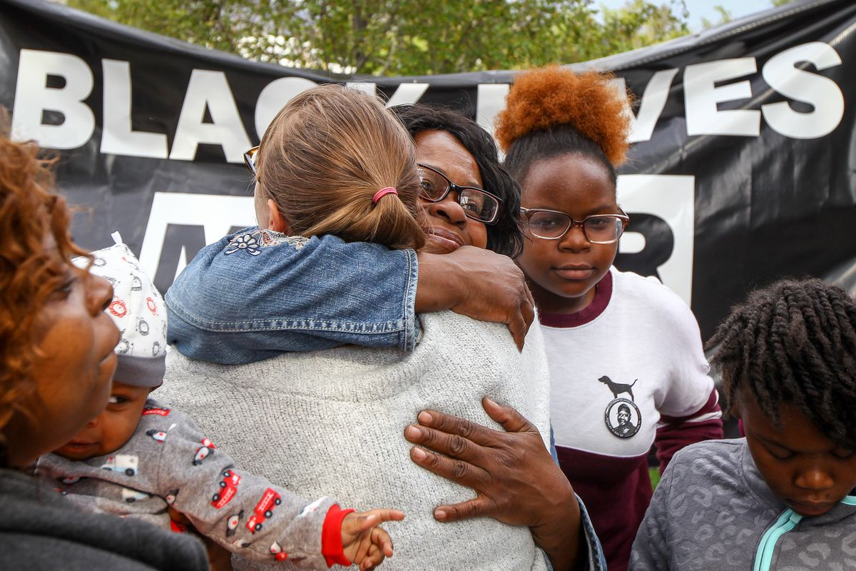 FILE - Supporters hug members of Patrick Harmon's family at the rally demanding justice for the August death of Patrick Harmon at the Public Safety Building in Salt Lake City Saturday, Sept. 30, 2017. The children of Patrick Harmon, a black man fatally sh