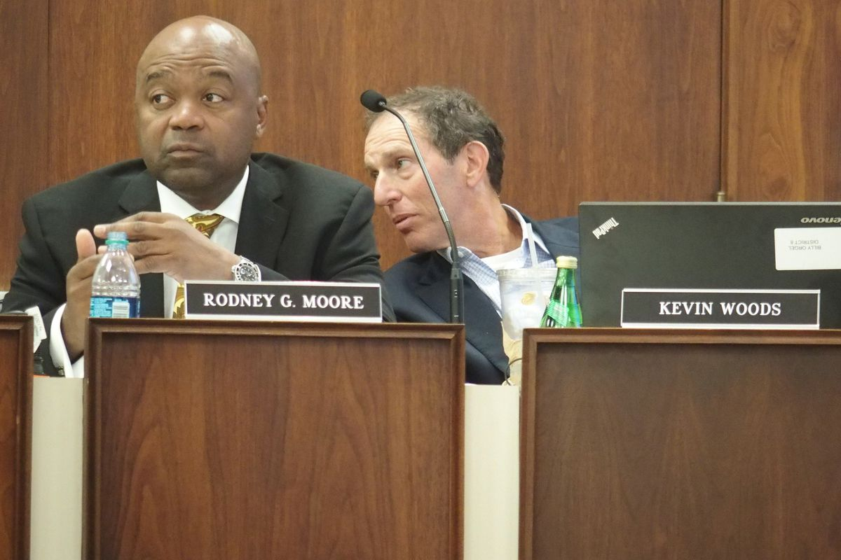 Rodney Moore and school board member Billy Orgel at an August meeting.