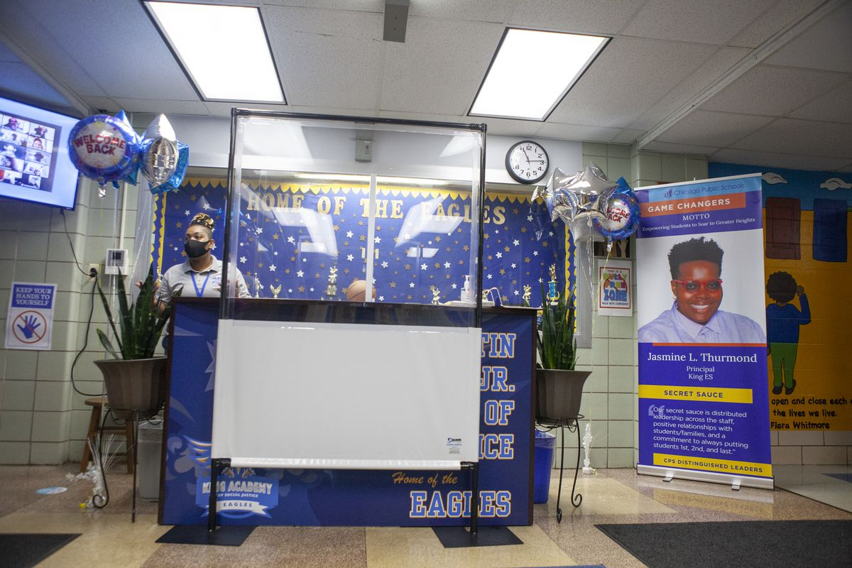 A health screening station with balloons that read welcome back.