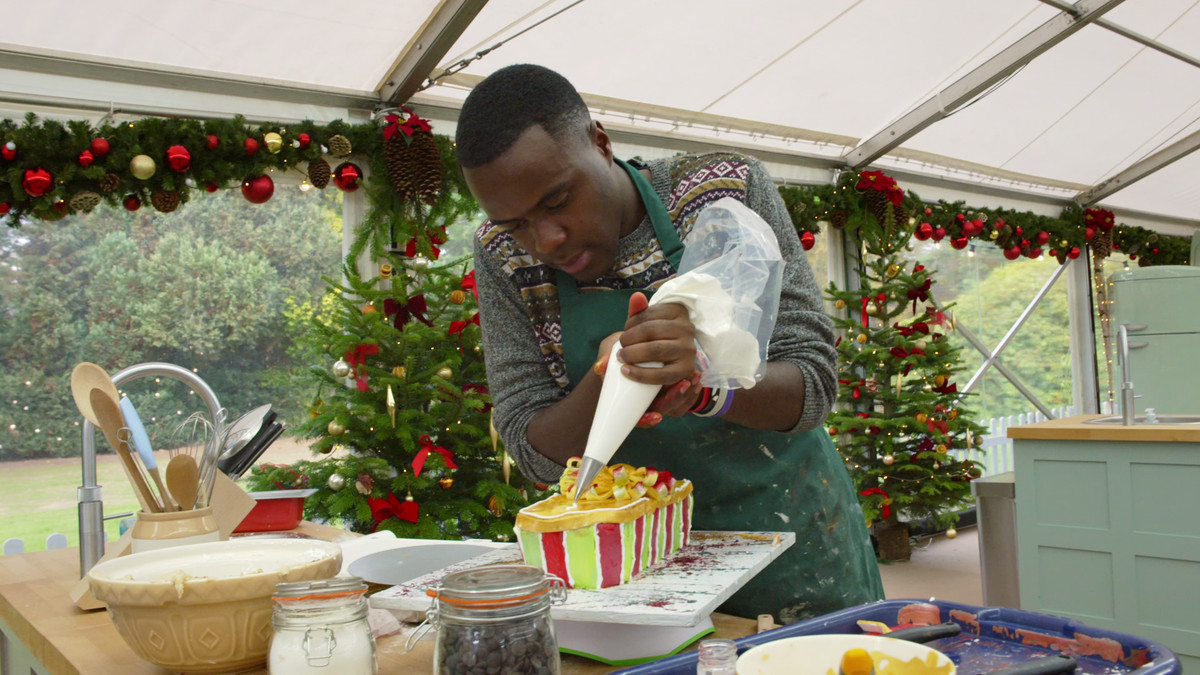 a baker frosts a cake on the great british bake off