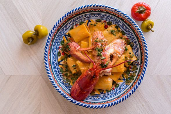 A blue bowl with pasta and lobster