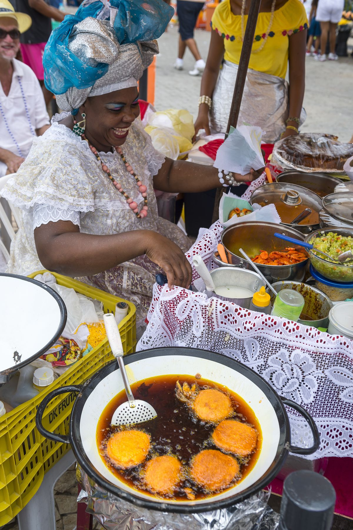 Brazilian Baiana woman assembles a plate of traditional acaraje fritters from a stall on the street.