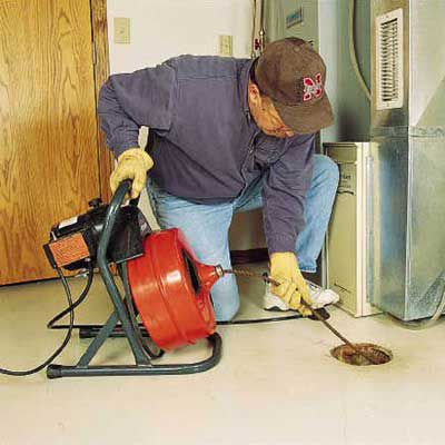 Person using a power auger to clear a floor drain.