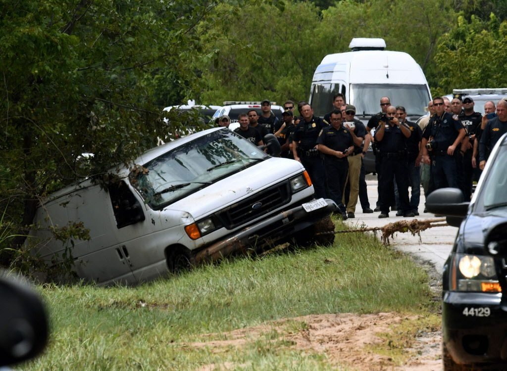 Police investigators watch as the van containing the six members of the the Saldivar family, who died, is towed to the road after they crashed their van into Greens Bayou as they tried to flee Hurricane Harvey during heavy flooding in Houston, Texas on Au