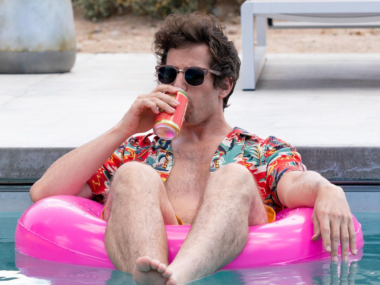 A man wearing sunglasses and a Hawaiian shirt floats in a pool drinking beer.