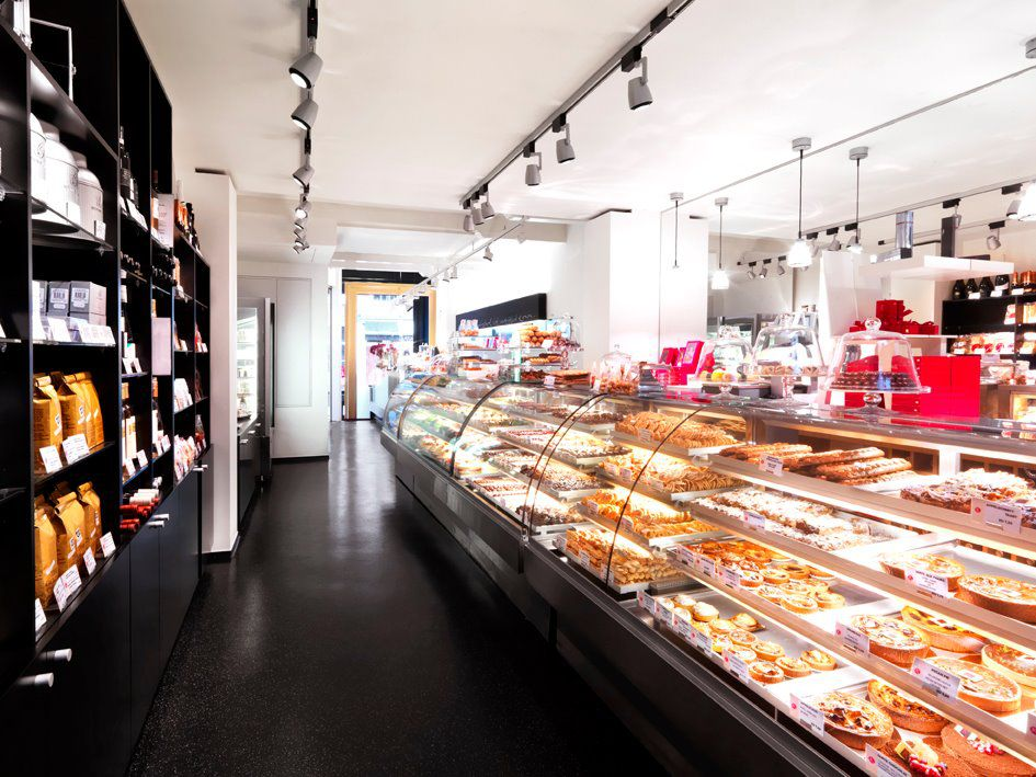 A long, lit-up pastry counter with cakes and other sweets visible, across from shelves of prepackaged goods.