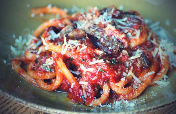 Closeup shot of thick pasta noodles covered in red sauce and grated parmesan cheese on a green ceramic plate.