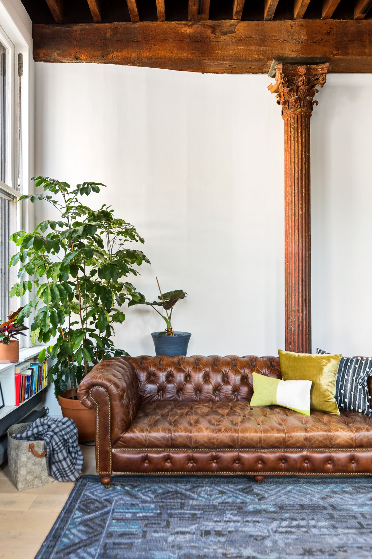 A living area with a brown leather couch, high ceilings, white walls, and a filigreed column in the back.