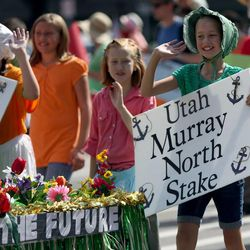Sophia Pickett, right, marches behind the Utah Murray North Stake float in the Days of '47 Youth Parade in Salt Lake City on Saturday, July 20, 2013.