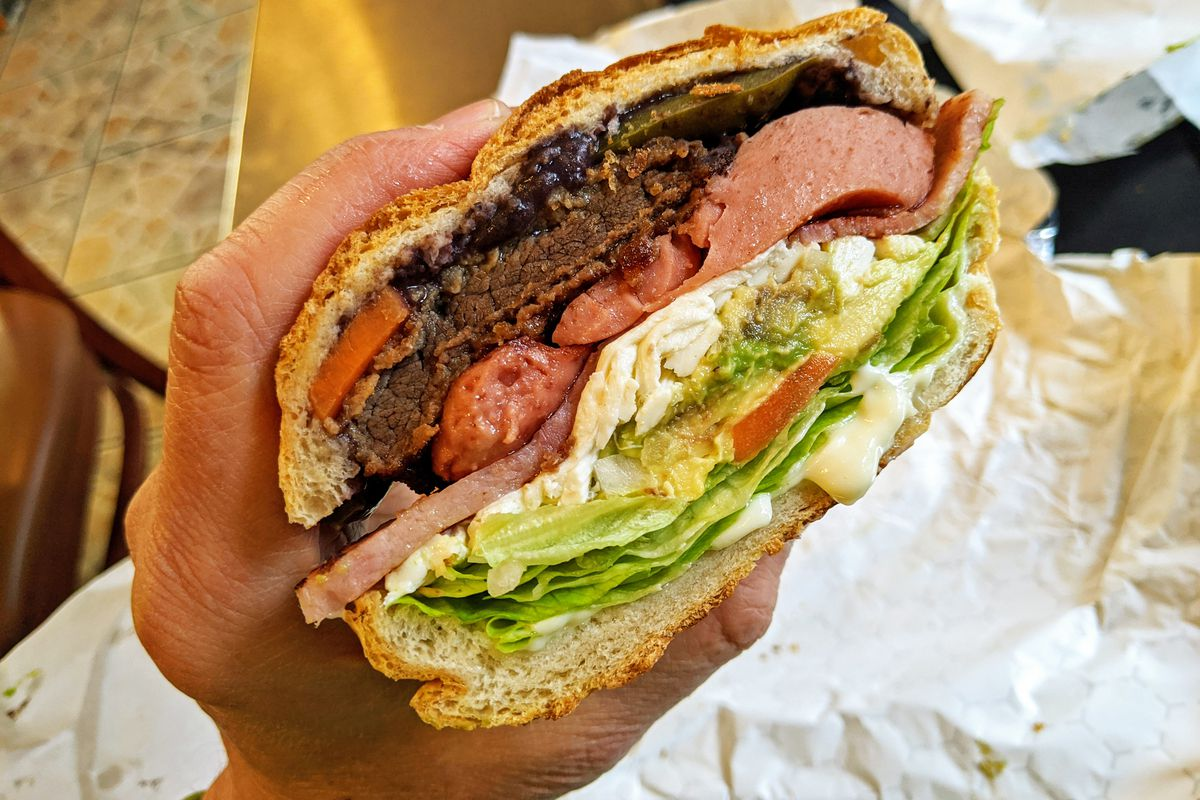 A hand holds a bulging sandwich with many colorful layers.