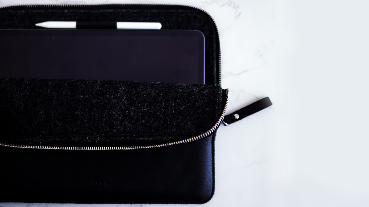A zipped open black leather case revealing an iPad and Apple Pencil.