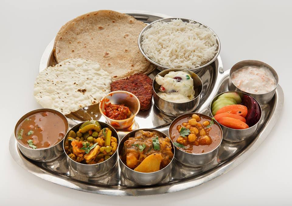 A metal tray features individual containers filled with different styles of flatbread, rice, and colorful chutneys.