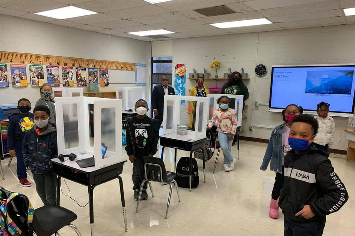 Students in masks pose standing next to their desks in a classroom at Germantown Elementary.
