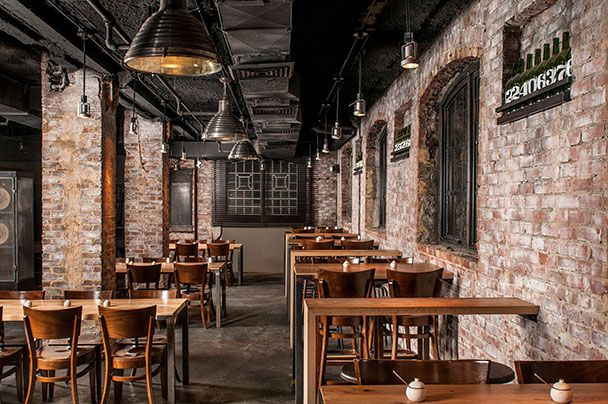 A dining and bar space in a basement with brick walls.