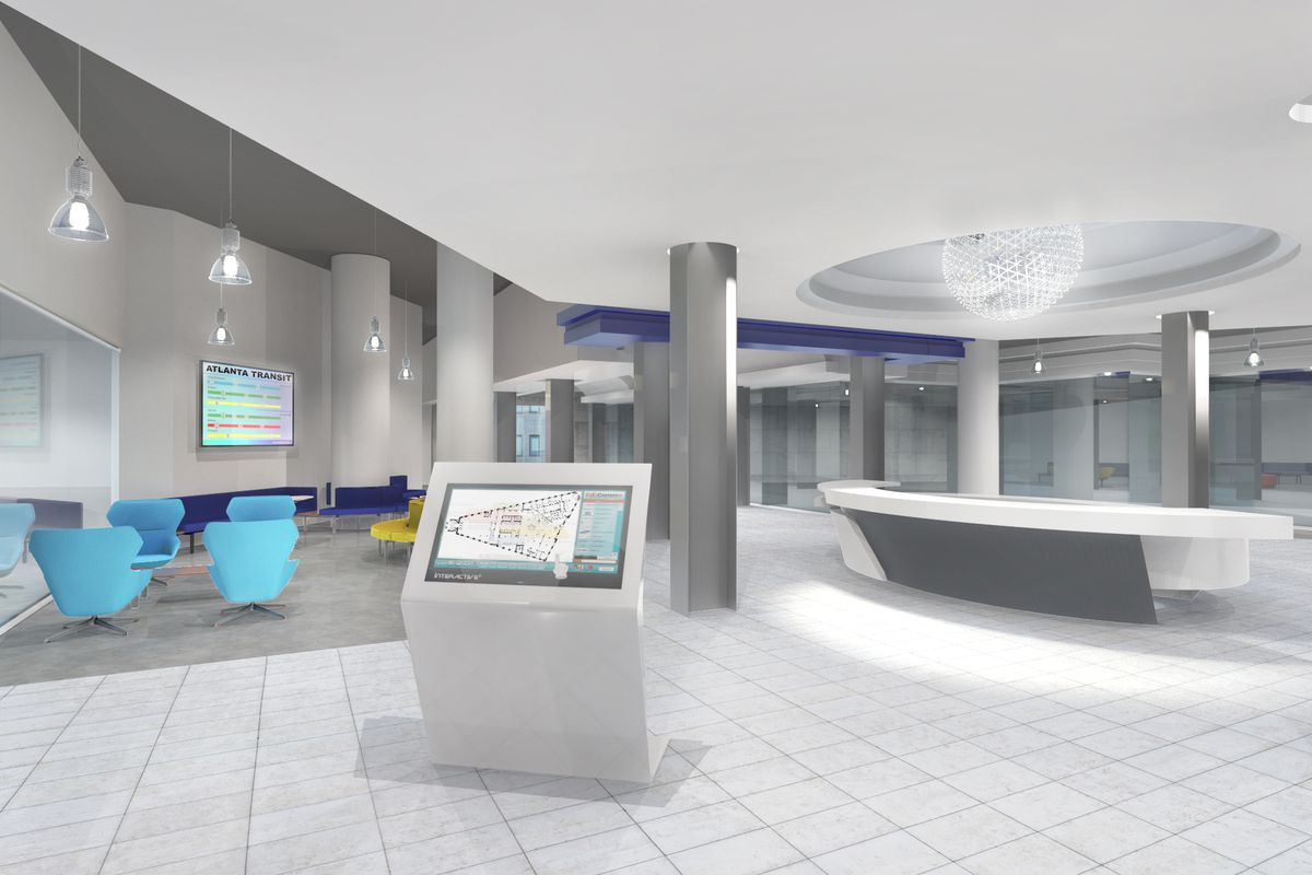 The interior of the Hurt Building. The floor, ceiling, and walls are white. There are blue chairs. There is a white lobby desk.