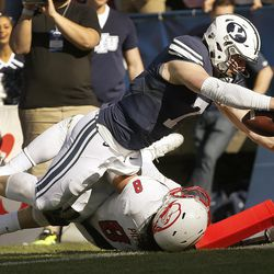 Brigham Young Cougars quarterback Taysom Hill (7) dives for a touchdwon over Southern Utah Thunderbirds defensive lineman Taylor Pili (8)  in Provo on Saturday, Nov. 12, 2016.