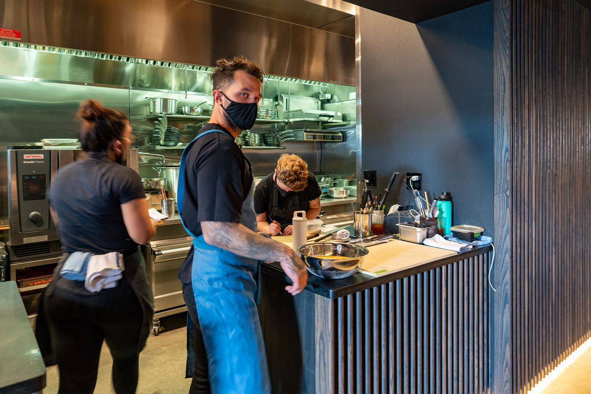 Chef Brady Williams wears a face mask and blue apron in the Tomo kitchen, while two other staffers work in the background.