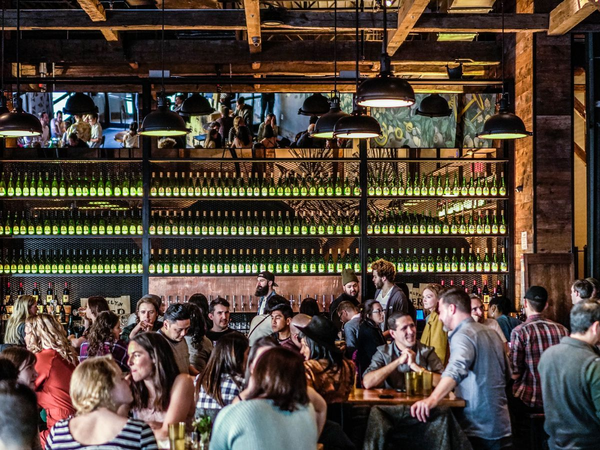Brooklyn Cider House's dining room has green bottles in the back and people sitting at tables in the front.