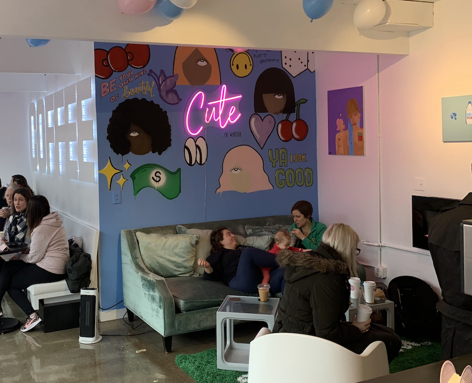 """A mural with a variety of faces and symbols, with """"Cute"""" in neon pink lighting."""