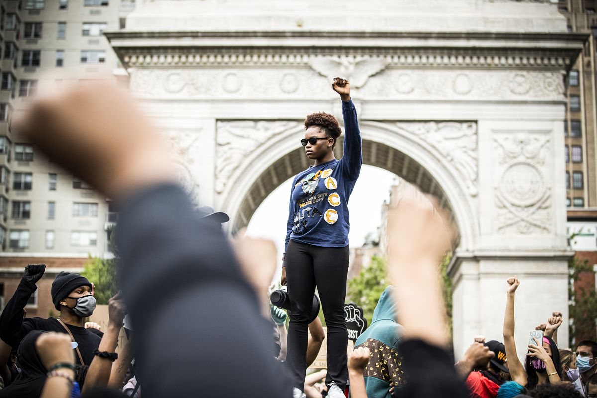 A woman in a blue shirt stands atop a pedestal, the park's famous stone arch behind her, and raises a fist. Around her, a crowd of protesters raise their fists as well.