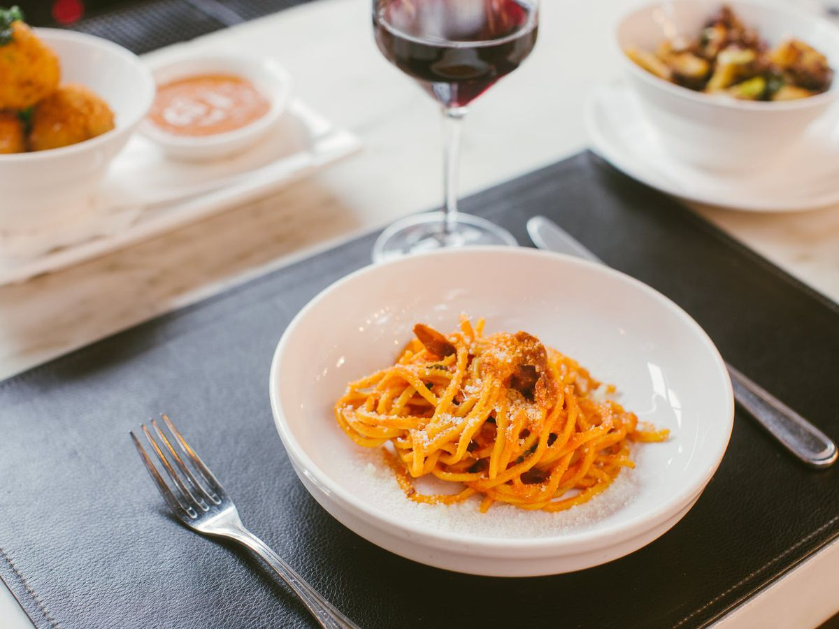 Plate of fresh spaghetti with a glass of red wine