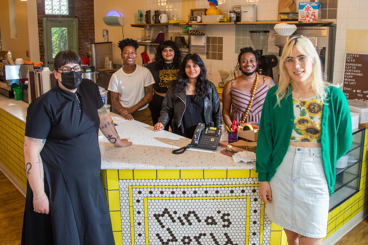 Six people stand in front of a coffee shop counter with yellow tile and black and white writing that says mina's world
