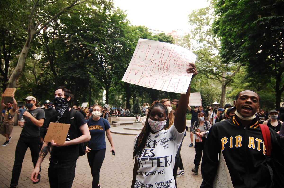 """A protester holds up a sign reading """"Black lives matter."""""""