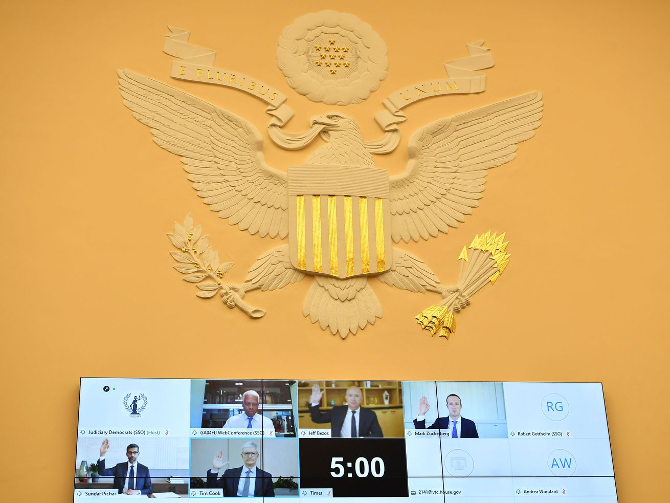 A screen with tech CEOs sits beneath the Great Seal of the United States.