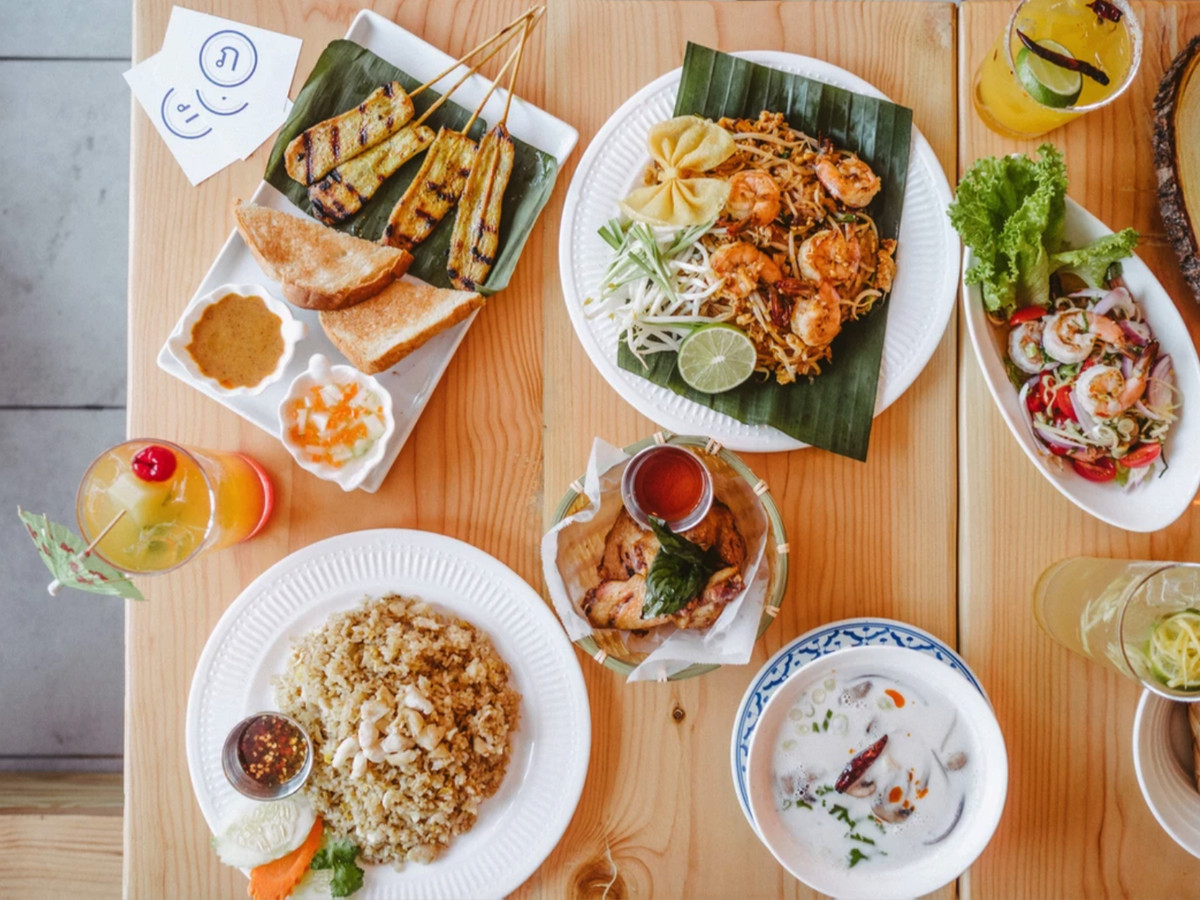 A spread of Thai food on a blonde wooden table, including skewers and rice.