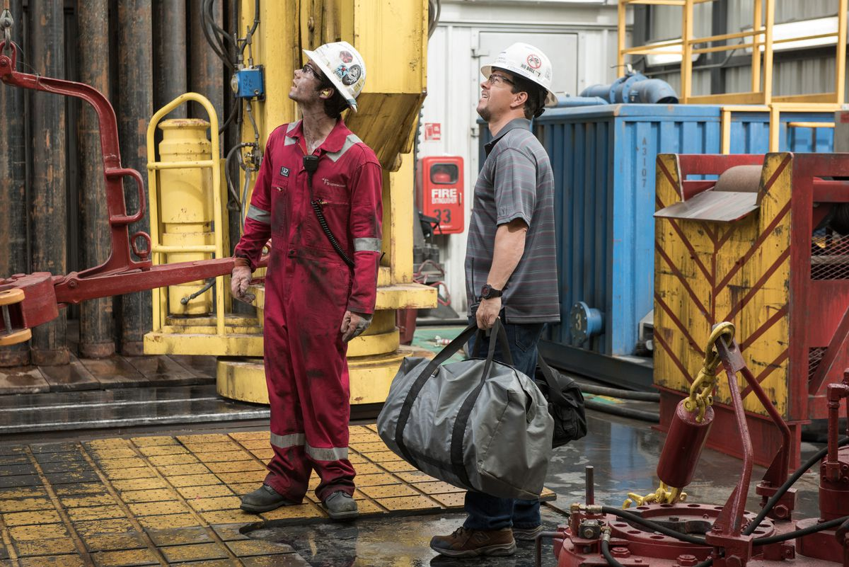 Two engineers look up at the rig.