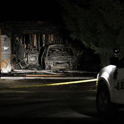 With a Sheriff's vehicle at right, charred walls and a burned automobile show at the home of Josh Powell in Puyallup, Washington, Sunday, Feb. 5, 2012.