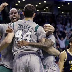Boston Celtics center Tyler Zeller (44) celebrates with teammates Luigi Datome, left, and Isaiah Thomas, right, after he hit the game-winning shot in second half of an NBA basketball game against the Utah Jazz in Boston, Wednesday, March 4, 2015. The Celtics won 85-84. Utah Jazz center Rudy Gobert (27) reacts at right. (AP Photo/Elise Amendola)