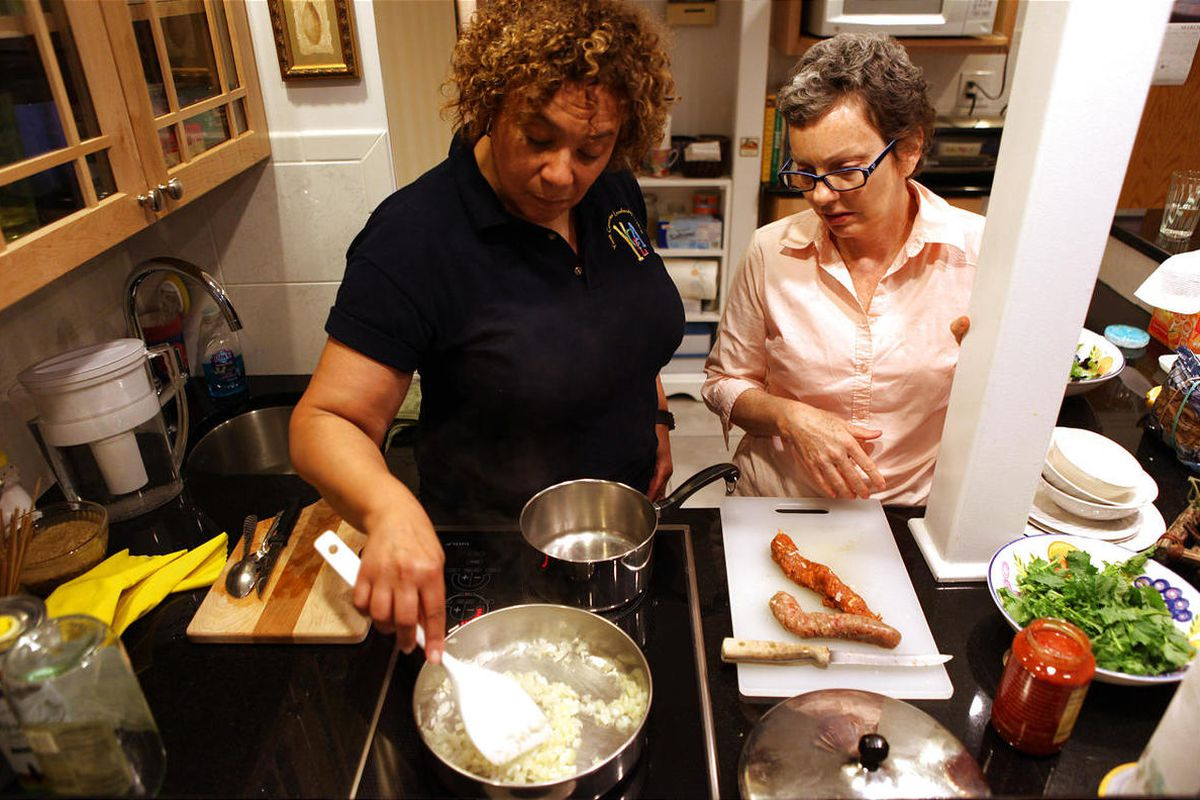 Sevara Cruzat, left, helps her friend Claudia Peyto make dinner for both at Peyton's apartment in Chicago, Illinois, on Friday March 23, 2012. Peyton is recovering from breast cancer, and Cruzat is one of many friends that pitches in to help Peyton.