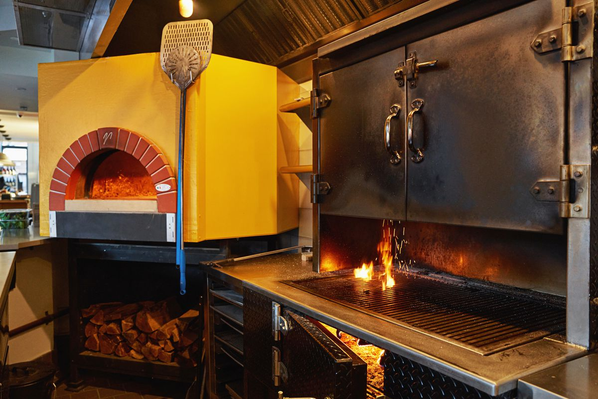 A photo of a wood-fired grill and a pizza oven side by side