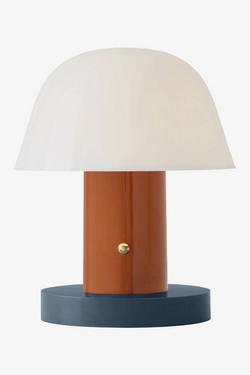 Lamp with round blue and brown base, and white shade.