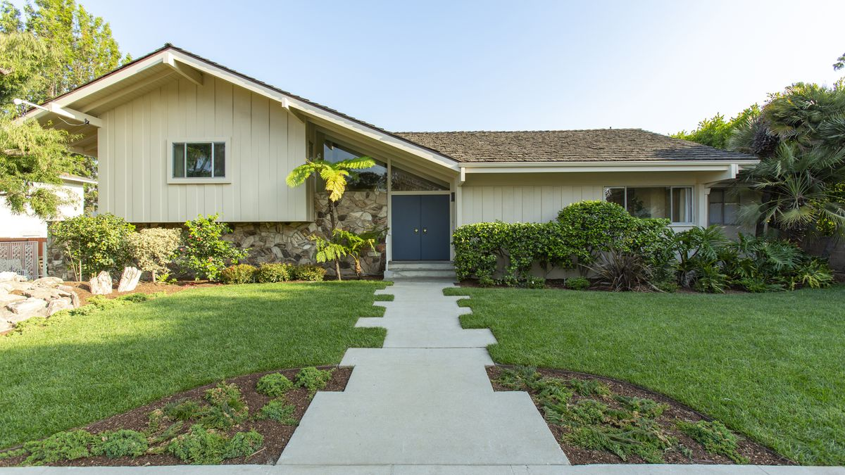 The facade of a midcentury home with an off-set pitched roof, clapboard siding, and partial stone facade. The double-front door is painted blue. The home is fronted by a deep lawn.