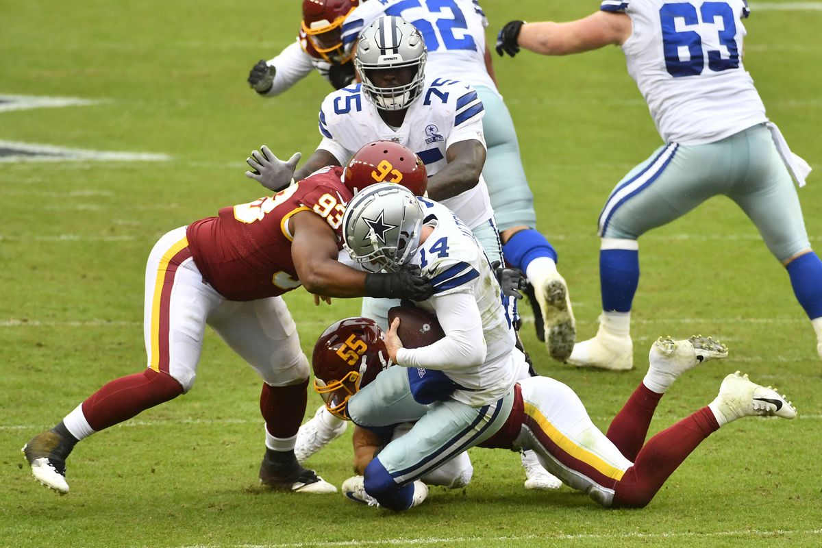 Dallas Cowboys quarterback Andy Dalton (14) is sacked by Washington Football Team defensive tackle Jonathan Allen (93) and linebacker Cole Holcomb (55) during the first half at FedExField.