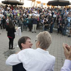 Cody Partridge, center left, hugs her wife, Laurie Wood, during a same sex marriage celebration at Library Square in Salt Lake City, Monday, Oct. 6, 2014.