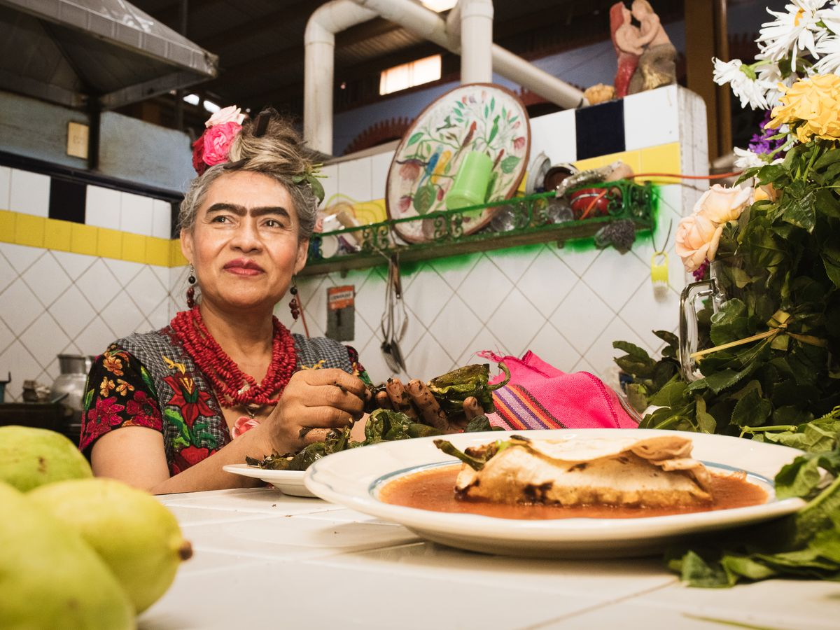 A woman dressed as Frida Kahlo sitting at a table with food.