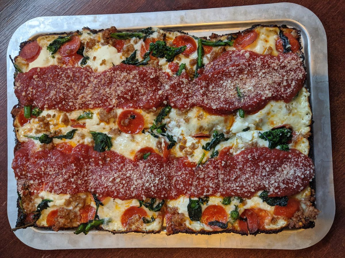 Overhead view of a rectangular Detroit-style pizza with broccoli rabe and pepperoni visible under two thick strips of red sauce