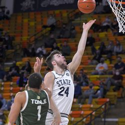Utah State guard Rollie Worster (24) shoots as Colorado State guard John Tonje (1) defends during the first half of an NCAA college basketball game Thursday, Jan. 21, 2021, in Logan, Utah.