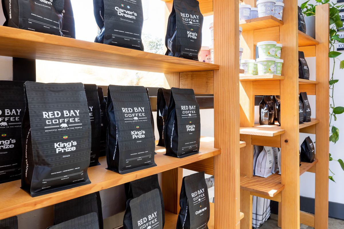 Bags of Red Bay Coffee beans on a brown wooden shelf.