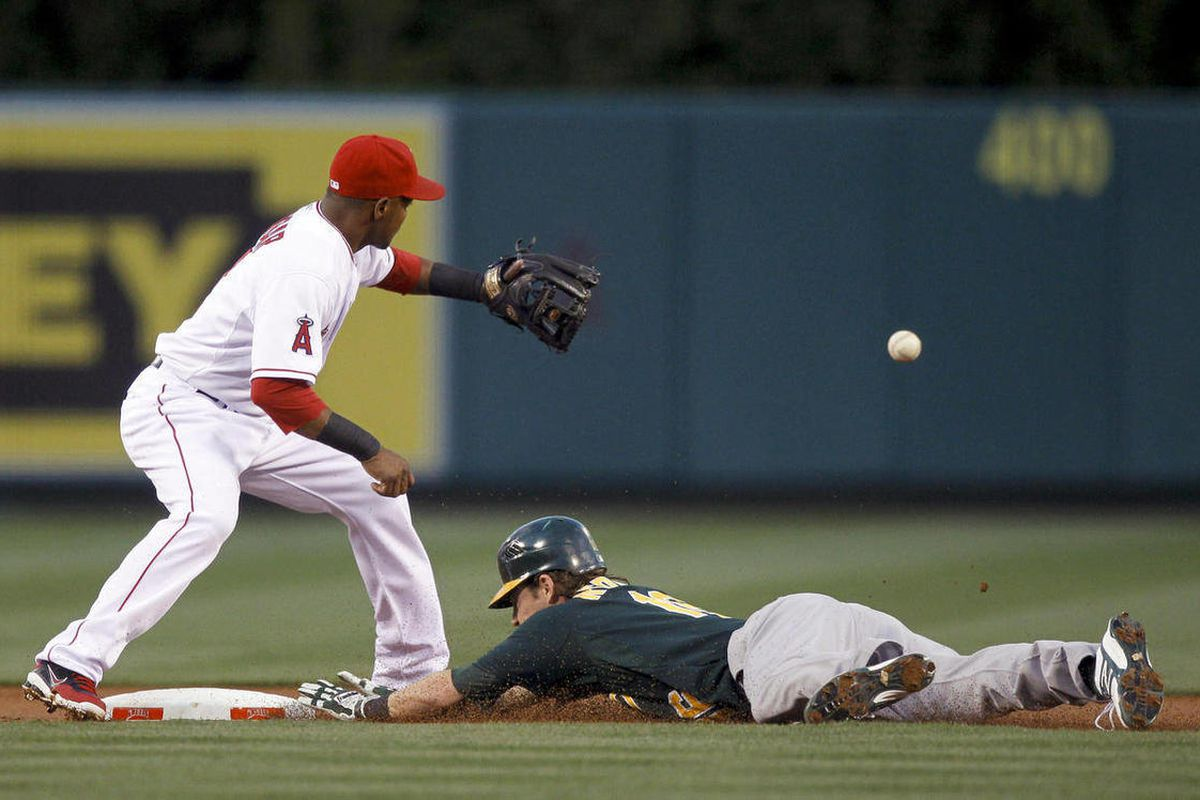 Oakland Athletics' Josh Reddick, right, is safe at second after a double as Los Angeles Angels shortstop Erick Aybar waits for the throw during the first inning of a baseball game in Anaheim, Calif., Tuesday, April 17, 2012.