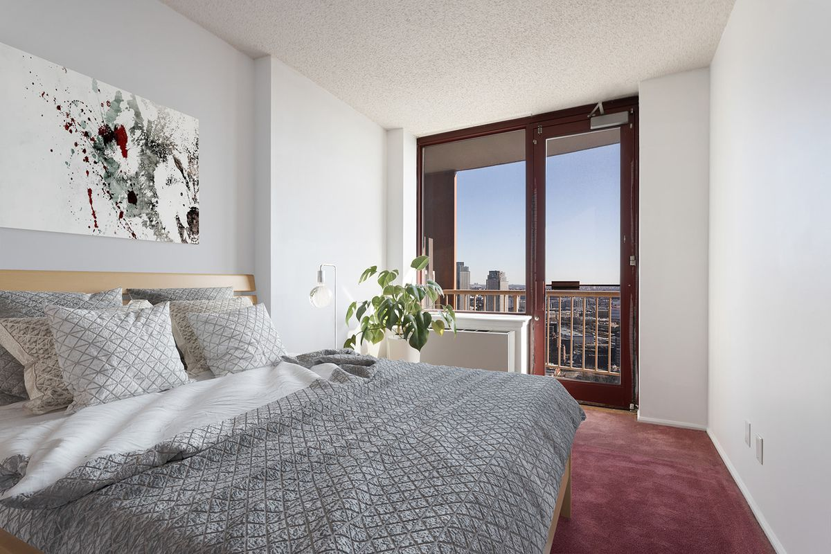 A bedroom with a large bed, a door that leads to a balcony, and a red rug.