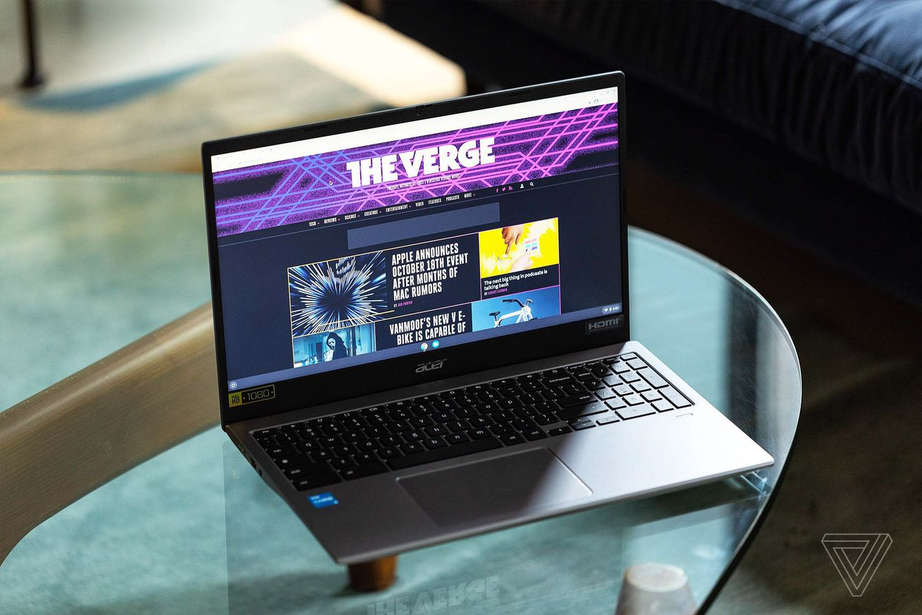 The Acer Chromebook 515 open, to the right, on a clear table. The screen displays The Verge homepage.